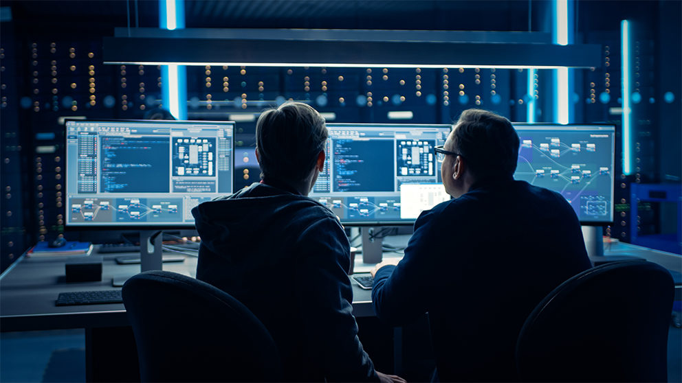 Two men in a server room, looking at computer screens