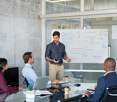 Group of three men brainstorm with a whiteboard