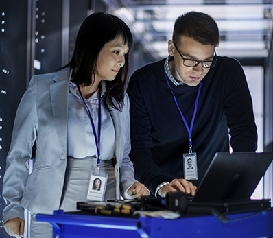 Two professionals work over a laptop